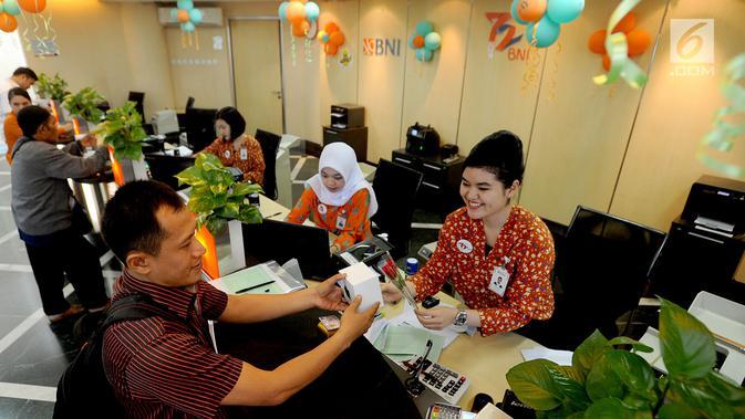 Teller memberikan bunga mawar dan souvenir kepada nasabah di Kantor Cabang BNI Tebet, Jakarta (5/7). Kegiatan dalam rangka HUT ke 72 BNI mengusung tema BNITu Digital. (Dailymail.co.id/Arie Basuki)