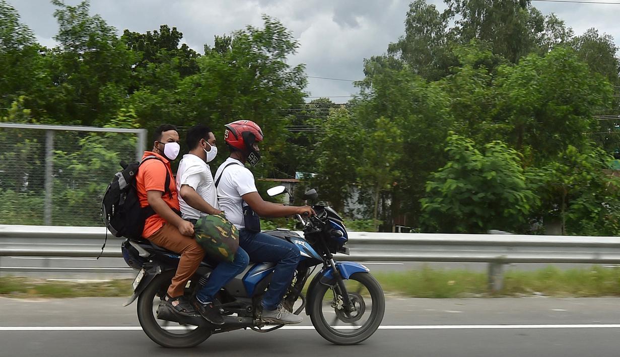 Orang-orang mengendarai sepeda motor menuju kampung halaman mereka setelah pelonggaran lockdown nasional COVID-19 di Sreenagar, Selasa (13/7/2021). Pemerintah Bangladesh telah memutuskan melonggarkan lockdown selama seminggu mulai 15 hingga 22 Juli untuk perayaan Idul Adha. (Munir Uz zaman/AFP)