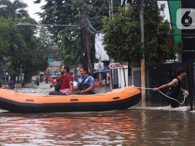 Warga menaiki perahu karet melintasi banjir yang merendam kawasan Benhil, Jakarta, Selasa (25/2/2020). Hujan yang mengguyur wilayah tersebut membuat air sungai meluap sehingga menyebabkan Banjir setinggi pinggang orang dewasa. (Liputan6.com/Angga Yuniar)