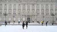 Dua gadis berlari melewati salju di luar Istana Kerajaan, Madrid, Spanyol, Jumat (8/1/2021). Salju tebal menutupi hingga setengah dari Spanyol dan menyebabkan penurunan suhu yang besar. (GABRIEL BOUYS/AFP)