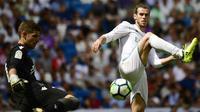 Aksi pemain Real Madrid, Gareth Bale (kanan)  mengadang sepakan kiper Levante, Raul Fernandez pada lanjutan La Liga di Santiago Bernabeu stadium, Madrid (9/9/2017). Madrid bermain imbang 1-1. (AFP/Pierre-Philippe Marcou)
