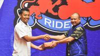 Kapten Arema Cronus, Hamka Hamzah, tersenyum menerima kucuran bonus dari pembina klub, Teddy Minahasa. (Bola.com/Iwan Setiawan)