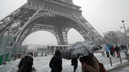 Pejalan kaki berjalan di dekat Menara Eiffel saat turun salju di Paris, Prancis, (6/2). Badan cuaca nasional Prancis Meteo France mengatakan sekitar setengah negara di eropa siaga atas bahaya tingkat salju dan es yang berbahaya. (AP Photo / Francois Mori)