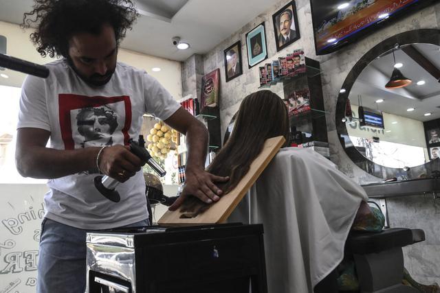 Dalam gambar pada 8 April 2021, tukang cukur Pakistan Ali Abbas menggunakan obor las untuk memotong rambut seorang pelanggan di tokonya di Lahore. Berharap membuktikan kemampuannya dalam persaingan, Ali Abbas mengandalkan berbagai alat yang tidak biasa untuk melatih keahliannya. (Arif ALI/AFP)