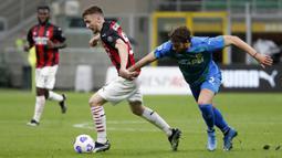 Striker AC Milan, Alexis Saelemaekers (kiri) menguasai bola dibayangi bek Sassuolo, Federico Peluso dalam laga lanjutan Liga Italia 2020/2021 pekan ke-32 di San Siro Stadium, Milan, Rabu (21/4/2021). AC Milan kalah 1-2 dari Sassuolo. (AP/Antonio Calanni)