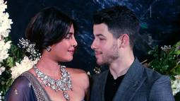 Pasangan aktris Bollywood Priyanka Chopra dan musisi Nick Jonas berpose untuk resepsi kedua pernikahan mereka di Mumbai, India, Rabu (19/12). Malam itu, Priyanka Chopra mengenakan gaun biru navy tanpa tali dengan sulaman emas. (AP/Rajanish Kakade)