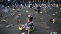 Seorang anak duduk bersama ratusan boneka saat menggelar aksi memprotes penganiayaan terhadap anak sekaligus meningkatkan kesadaran akan tanggung jawab dalam perlindungan anak di Alun-alun Bolivar, Bogota, Kolombia (20/11). (AFP Photo/Raul Arboleda)