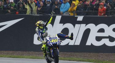 Pebalap Movistar Yamaha, Valentino Rossi, merajai lintasan basah dengan memenangi MotoGP Inggris, Minggu (30/8/2015). Rossi finis pertama di Sirkuit Silverstone, Inggris. (Reuters/Darren Staples)