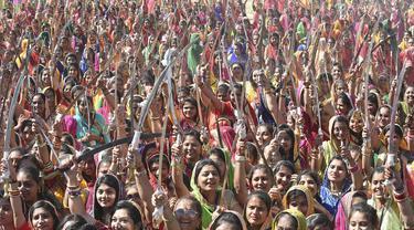 Wanita dari komunitas Shatriya menari dengan pedang dalam upaya untuk menetapkan rekor dunia dalam tarian pedang  di Rajkot,  Ahmedabad, India (28/1/2020). Acara ini bagian dari upacara penobatan tiga hari raja Rajkot ke-17, Thakorsaheb Mandhatasinh Jadeja. (AFP/Sam Panthaky)