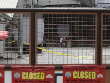 Dua pria berdiskusi di dalam kompleks Pabrik Es TP Marcelo di Navotas, Filipina, Kamis (4/2/2021). Kebocoran gas amonia terjadi di sebuah pabrik es di wilayah Manila, ibu kota Filipina. Kejadian itu menewaskan dua orang dan lebih dari 90 lainnya terluka atau jatuh sakit. (AP Photo/ Aaron Favila)