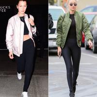 Bella Hadid dan Gigi Hadid kompak banget pakai jaket bombers dan legging saat jalan-jalan. (SPLASH NEWS; FAMEFLYNET/InStyle)