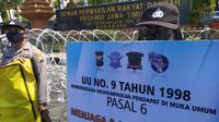 Sejumlah Polwan membawa spanduk bertuliskan Satlantas Polrestabes Surabaya cinta damai saat mengamankan demo UU Cipta Kerja, Kamis (22/10/2020). (Foto: Liputan6.com/Dian Kurniawan)