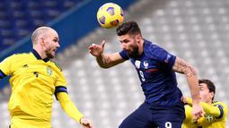 Penyerang Prancis, Olivier Giroud, menyundul bola saat menghadapi Swedia pada laga lanjutan Grup 3 UEFA Nations League di Stade de France, Rabu (18/11/2020) dini hari WIB. Prancis menang 4-2 atas Swedia. (AFP/Franck Fife)