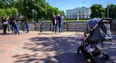 Turis dan warga mengunjungi Lafayette Square dekat Gedung Putih di Washington, DC, pada Selasa (10/5/2021). Lafayette Square dibuka kembali untuk pejalan kaki hampir setahun setelah daerah itu dipagari ketika demonstrasi semakin besar sebagai tanggapan atas kematian George Floyd. (Eric BARADAT/AFP)