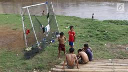 Anak-anak beristirahat usai bermain sepak bola di bantaran Kanal Banjir Barat, Jakarta, Jumat (5/4). Tidak adanya lapangan menjadikan lokasi tersebut sebagai tempat bermain mereka, meskipun dalam kondisi seadanya. (Liputan6.com/Immanuel Antonius)
