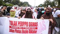 Peserta aksi wanita membentangkan spanduk saat berunjuk rasa di Pintu Barat Monas, Jakarta, Selasa (18/7). (Liputan6.com/Faizal Fanani)