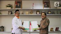 Direktur KSKK Madrasah Ditjen Pendis Kemenag Dr. A. Umar, M.A (kiri) dan Presdir Smartfren Merza Fachys (kanan) usai menandatangani nota kerjasama pemberian kartu perdana Smartfren gratis untuk Madrasah se-Indonesia untuk mendukung program PJJ, di Jakarta, Senin (21/9/2020). (Liputan6.com/HO/Agus)