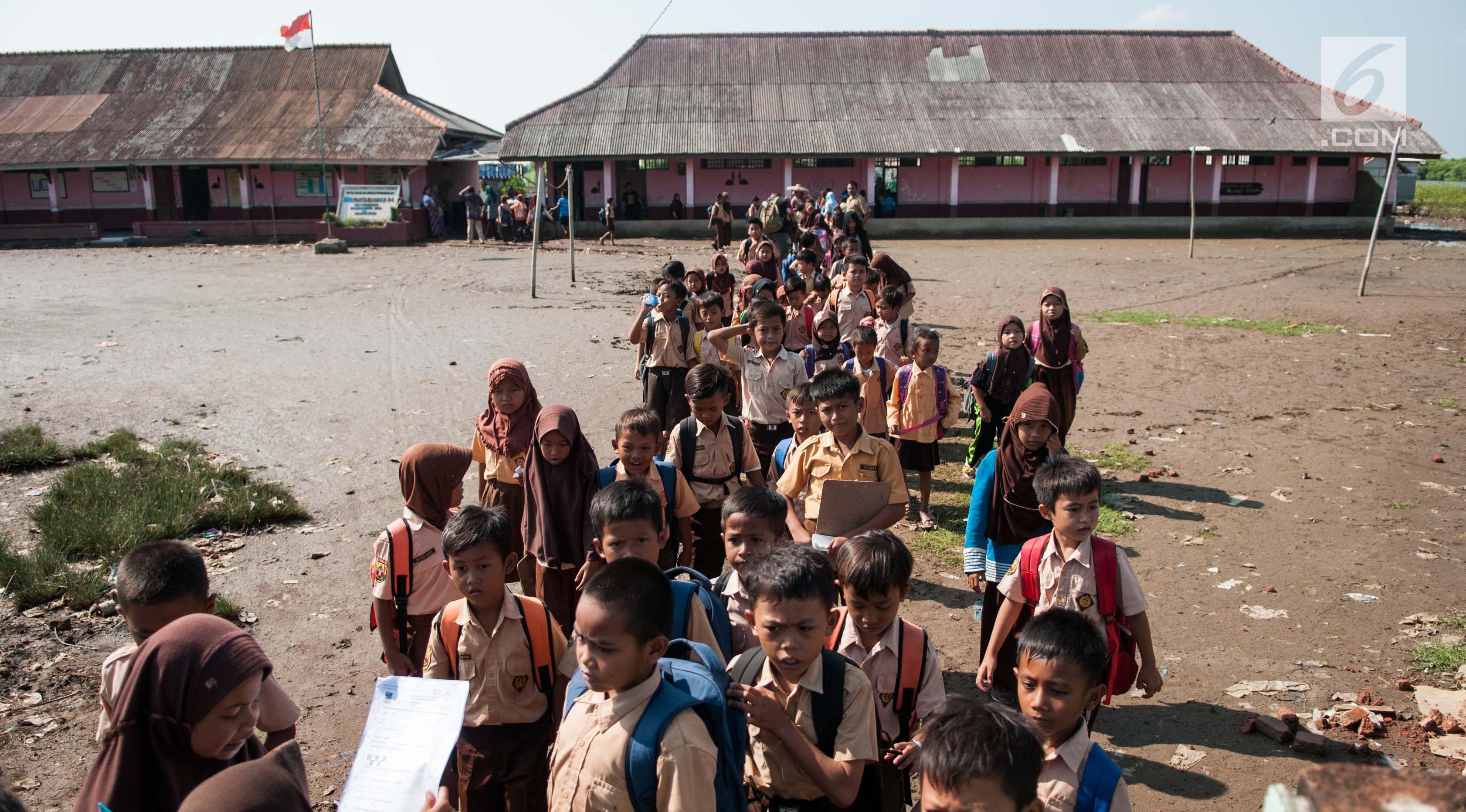 Sejumlah siswa keluar kelas usai kegiatan belajar mengajar selesai di SDN 04 Pantai Bahagia, Muara Gembong, Jawa Barat, Jumat (9/6). Banjir Rob yang sering melanda kawasan ini menyebabkan kondisi bangunan memprihatinkan. (Liputan6.com/Gempur M Surya)