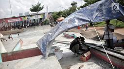 Pekerja memperbaiki arena skateboard yang rusak di RPTRA Kalijodo, Jakarta, Kamis (24/1). Perbaikan dilakukan untuk membuat rasa aman dan nyaman pengunjung yang menggunakan arena tersebut. (Liputan6.com/Faizal Fanani)