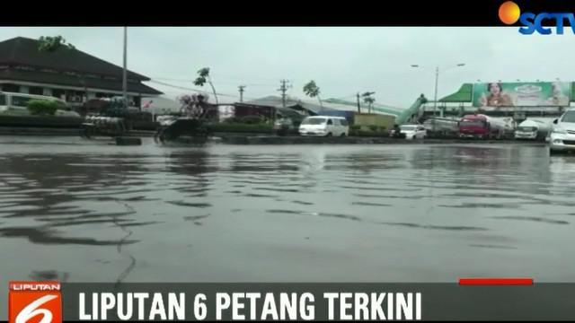 Kendaraan yang melintas harus mengurangi laju kecepatan saat menerabas genangan air.
