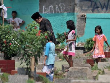 Sejumlah anak mengikuti peziarah saat menawarkan jasa membersihkan makam atau 'Ngoret' di TPU Cipinang Baru, Jakarta, Minggu (5/5). Tradisi ziarah makam atau nyekar membawa berkah rezeki bagi anak-anak yang menawarkan jasa Ngoret. (merdeka.com/Iqbal S. Nugroho)