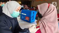 Paramedis melakukan penyuntikan vaksin Covid-19 kepada guru di Teraskota Mall. Tangerang Selatan, Banten, Rabu (28/04/2021). Vaksinasi dalam rangka persiapan kegiatan belajar tatap muka secara terbatas di wilayah Tangsel pada Juli mendatang. (merdeka.com/Arie Basuki)