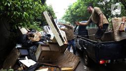 Petugas membuang barang milik warga di sepanjang jalan pascabanjir mulai surut di kawasan Kembangan, Jakarta Barat, Minggu (5/1/2020). Pasca banjir yang melanda hampir di kawasan Jakarta mulai surut, tumpukan sampah terlihat di sepanjang jalan dari rumah-rumah warga. (Liputan6.com/Johan Tallo)