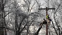 Seorang pekerja memperbaiki kabel listrik saat badai musim dingin di West Orange, New Jersey (18/12/2019). Badai musim dingin membawa malapetaka ke New Jersey ketika es menyebabkan pemadaman listrik dan menumbangkan pohon di seluruh wilayah tersebut. (Rick Loomis/Getty Images/AFP)