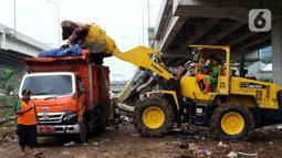 Petugas PPSU DKI Jakarta menggunakan alat berat saat mengangkut sampah sisa banjir di bawah Tol Becakayu, Cipinang Melayu, Jakarta Timur, Rabu (8/1/2020). Sampah sisa banjir tersebut selanjutnya diangkut ke TPA Bantar Gebang. (merdeka.com/Magang/Muhammad Fayyadh)