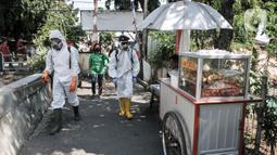 Petugas Palang Merah Indonesia (PMI) Jakarta Timur berpakaian APD menyemprotkan disinfektan di permukiman Kampung Tengah, Kramat Jati, Minggu (23/8/2020). Penyemprotan sebagai langkah sterilisasi permukiman setelah warga di Kampung Tengah dilaporkan terpapar Covid-19. (Liputan6.com/Iqbal Nugroho)