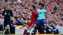 Pemain Bournemouth Nathan Ake berusaha menghadang pemain Liverpool Mohamed Salah saat pertandingan Liga Inggris di Anfield, Liverpool (14/4). Liverpool meraih kemenangan telak pada laga kandang melawan Bournemouth. (Anthony Devlin/PA via AP)
