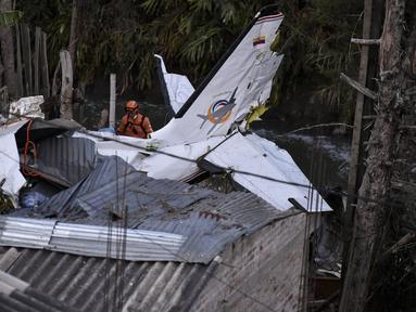 Tim penyelamat berada di lokasi jatuhnya sebuah pesawat kecil di tengah-tengah rumah penduduk di Popayan, Kolombia, Minggu (15/9/2019). Insiden tersebut mengakibatkan tujuh dari sembilan penumpang tewas. (Luis ROBAYO / AFP)
