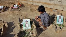 Seorang anak berdoa di makam anak-anak sekolah di sebuah pemakaman di provinsi kubu pemberontak Huthi di Saada (4/9). Anak-anak tersebut tewas terkena serangan udara koalisi pimpinan Saudi di pasar Dahyan pada bulan Agustus. (AFP Photo/Stringer)