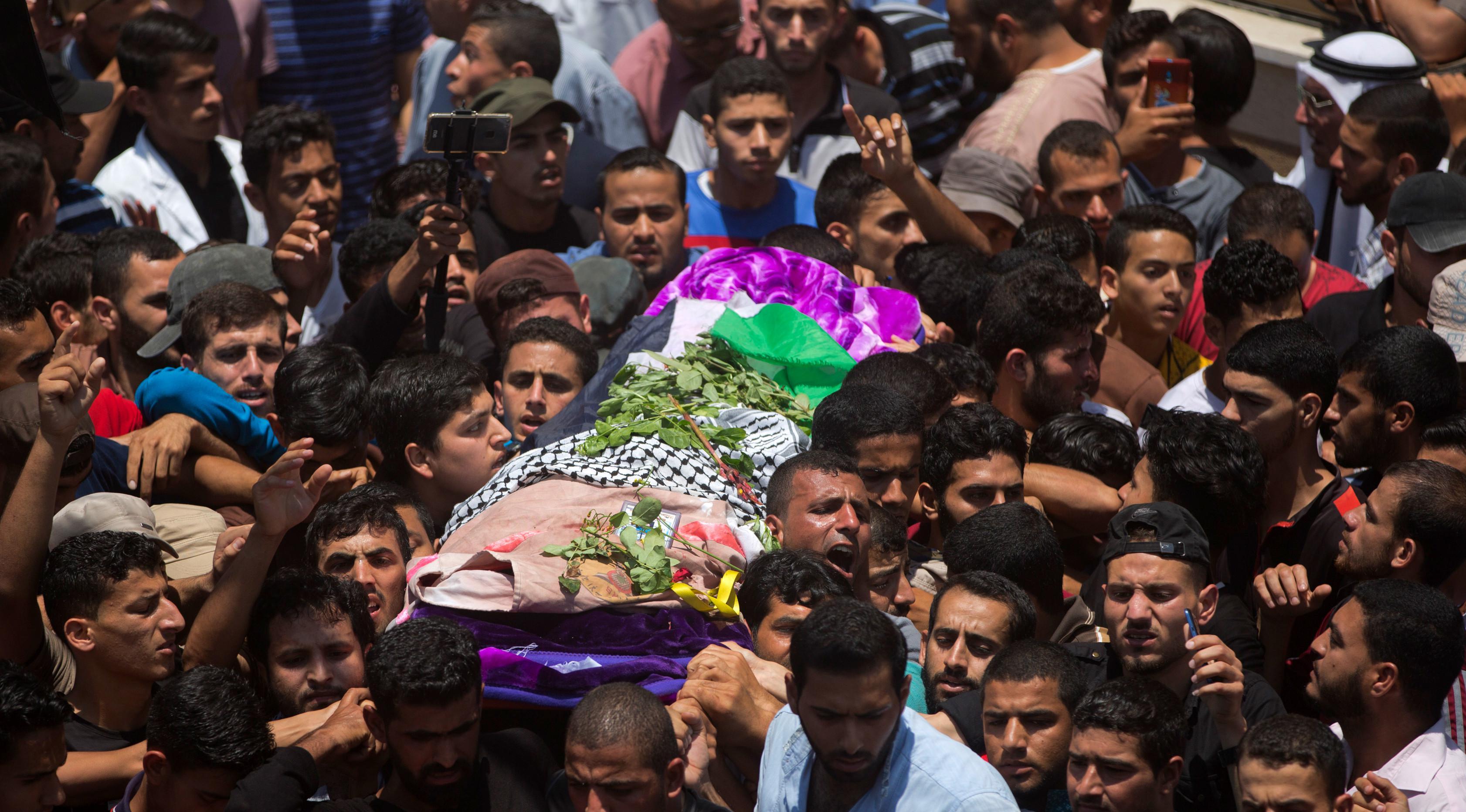 Ribuan pelayat membawa jasad perawat Palestina, Razan Najjar saat pemakamannya di Kota Khan Younis, Jalur Gaza Selatan, Sabtu (2/6). Gadis 21 tahun tersebut terbunuh oleh tembakan Israel pada Jumat, 1 Juni 2018. (AP Photo/Khalil Hamra)
