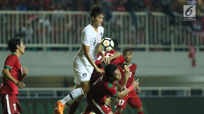 Pemain timnas Indonesia U-23 mencoba menghalangi pergerakan penyerang Korea Selatan U-23, Kim Jeung Ho pada laga persahabatan di Stadion Pakansari, Kab Bogor, Sabtu (23/6). Indonesia U-23 kalah 1-2. (Liputan6.com/Helmi Fithriansyah)#source%3Dgooglier%2Ecom#https%3A%2F%2Fgooglier%2Ecom%2Fpage%2F%2F10000