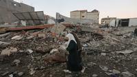 Dua wanit berjalana melewati puing-puing bangunan setelah serangan udara Israel di kota Gaza (27/10). Selain melancarkan serangan udara, Israel meluncurkan roket Iron Dome untuk menangkis rudal yang diluncurkan dari Palestina. (AFP Photo/Mahmud Hams)