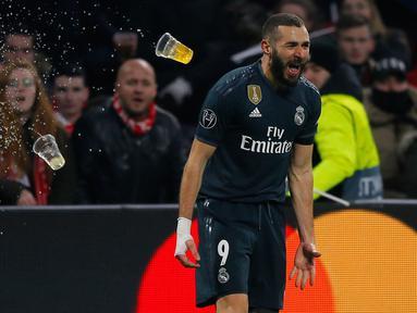Penyerang Real Madrid Karim Benzema berselebrasi setelah mencetak gol ke gawang Ajax pada leg pertama 16 besar Liga Champions di Johan Cruijff ArenA, Amsterdam, Rabu (13/2). Real Madrid harus bersusah payah menaklukkan Ajax, 2-1. (AP/Peter Dejong)