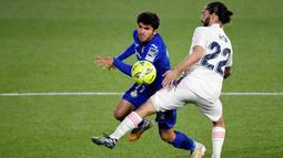 Gelandang Real Madrid, Isco, berusaha menghadang pemain Getafe, Carles Alena, pada laga Liga Spanyol di Stadion Alfonso Perez, Senin (19/4/2021). Kedua tim bermain imbang 0-0. (Photo by PIERRE-PHILIPPE MARCOU / AFP)