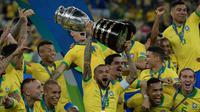 Pemain belakang timnas Brasil, Dani Alves mengangkat trofi Copa America 2019 saat berselebrasi bersama rekan setimnya setelah mengalahkan Peru pada partai final di Maracana Stadium, Rio de Janeiro, Senin (8/7/2019) dini hari WIB. Brasil menundukkan Peru dengan skor 3-1. (Juan MABROMATA/AFP)