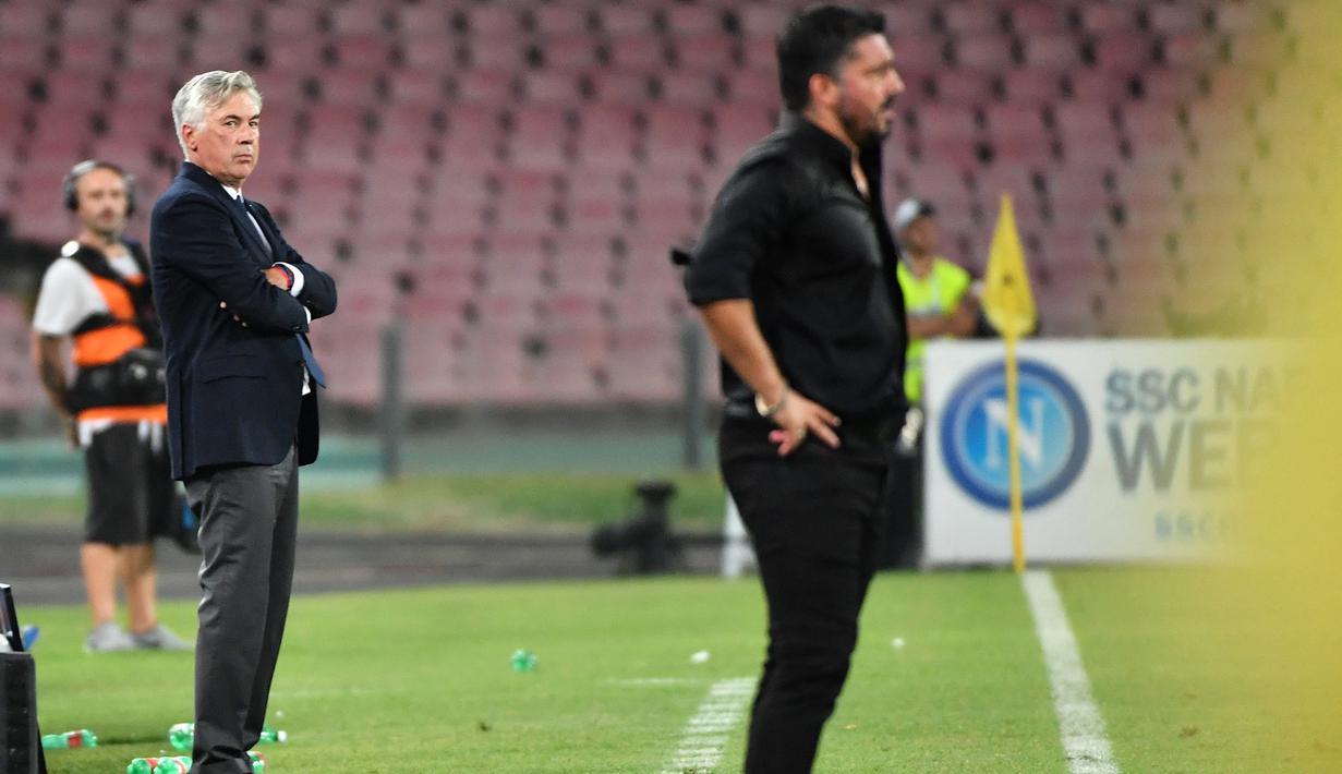 Pelatih Napoli, Carlo Ancelotti (kiri) dan pelatih AC Milan, Gennaro Gattuso melihat para pemainnya bertanding pada lanjutan Liga Serie A Italia di San Paolo Stadium, Naples (25/8). Napoli menang tipis atas Milan 3-2. (AFP Photo/Alberto Pizzoli)