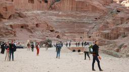 Wisatawan jalan-jalan saat mengunjungi kota arkeologi Petra, Yordania, Kamis (21/11/2019). Bangunan-bangunan di kota ini didirikan dengan memahat dinding-dinding batu di Wadi Araba, lembah bercadas di Yordania. (AHMAD ABDO/AFP)