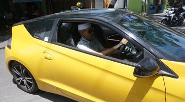 Kakeh Habib Hasan Mulachela dengan naik mobil sport Honda CR-Z bagi-bagi beras dan uang kepada warga tak mampu di Solo, Minggu (5/4).(Liputan6.com/Fajar Abrori)