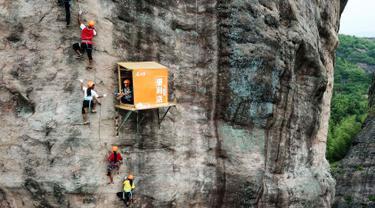 Sejumlah orang memanjat tebing melewati toko serba ada yang menempel di dinding tebing di Pingjiang di provinsi Hunan, China (25/4). Toko ini menjual minuman dan makanan untuk para pemanjat tebing yang melintas. (AFP Photo/China Out)