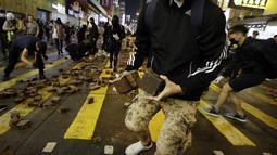 Pengunjuk rasa menggunakan mengumpulkan batu untuk mempersenjatai diri selama bentrokan dengan polisi di Mong Kok, Hong Kong (10/11/2019). Ketapel hingga panahan digunakan para demonstran Hong Kong sebagai senjata saat unjuk rasa yang telah berlangsung selama lima bulan. (AP Photo/Dita Alangkara)