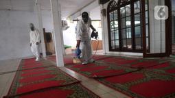 Petugas Dewan Masjid Indonesia (DMI) menyemprotkan cairan disinfektan di Masjid Hablul Muttaqin, Pejambon, Gambir, Jakarta Pusat, Jumat (6/3/2020). Kegiatan ini dilakukan untuk menjaga kebersihan masjid sekaligus mengantisipasi penyebaran virus corona (COVID-19). (Liputan6.com/Angga Yuniar)