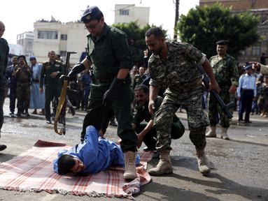 Pasukan keamanan bersiap mengeksekusi pria bernama Hussein al-Saket 22 tahun akibat memperkosa dan membunuh seorang gadis berusia empat tahun di alun-alun Tahrir, Ibu Kota Sanaa, Yaman (14/8). (AFP Photo/Mohammed Huwais)