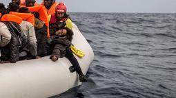 Seorang wanita saat diselamatkan petugas dari LSM Spanyol Proactiva Open Arms, setelah meninggalkan Libya yang mencoba mencapai tanah Eropa di atas sebuah kapal karet yang penuh sesak, 60 mil sebelah utara Al-Khums, Libya (18/2). (AP Photo/Olmo Calvo)