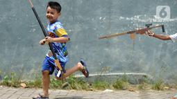 Anak-anak bermain senjata tembakan yang terbuat dari triplek bekas untuk mengusir kejenuhan usai belajar secara online di Parakan, Tangerang Selatan, Banten, Jumat (27/11/2020). Hampir 10 bulan mereka tidak melakukan aktivitas belajar tatap muka karena pandemi Covid 19. (merdeka.com/Dwi Narwoko)