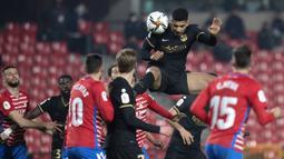 Bek Barcelona, Ronald Araujo (atas) menyundul bola dari ancaman pemain Granada dalam laga perempatfinal Copa del Rey 2020/21 di Nuevo Los Carmenes Stadium, Rabu (3/2/2021). Barcelona menang 5-3 (2-2) atas Granada melalui babak extra time. (AFP/Jorge Guerrero)