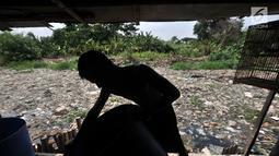 Warga beraktivitas di pinggiran Kali Pisang Batu yang dipenuhi sampah, Tarumajaya, Bekasi, Jawa Barat, Rabu (9/1). Warga tetap beraktivitas meski bau tak sedap menghantui mereka akibat tumpukan sampah di kali tersebut. (Merdeka.com/Iqbal S. Nugroho)